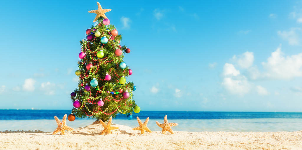 Subject: A decorated Christmas tree surrounded by dancing starfish on a tropical beach.